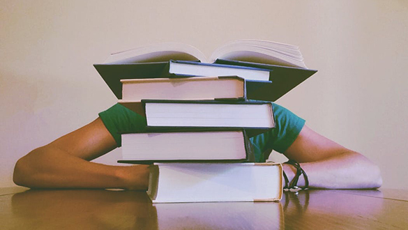 Student overwhelmed by stack of books
