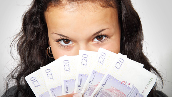 Girl holding fan of £20 notes